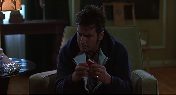 Screencap of Charlie fiddling around with a Rubik's Cube .