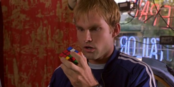 Screencap of Chester, who found a Rubik's cube in the pocket of his blue jogging suit. He is looking numb at it in a cloathing sture.