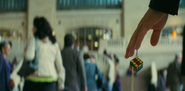 Screencap of Ray's hand, holding a Rubik's cube keychain.