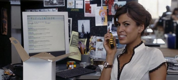 Eva Mendez holding a portophone while there is a Rubik's cub on her desk.