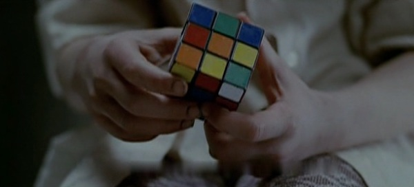 Screencap of Eli who is trying to solve the Rubik's cube. The shot is made of only the hands and the Rubik's cube.