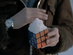 Screencap of Oskar with a solved Rubik's cube in his hand. There is a certain amount of snow on top of the cube, since it is winter.