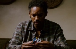 Screencap of Chris trying to solve the Rubik's cube, while sitting on the couch. The shot is made van up-front.