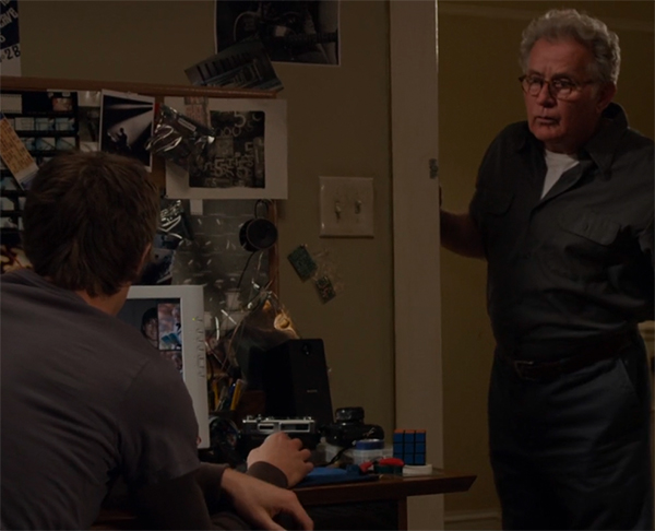 Uncle Ben standing in the doorway, next to a desk with lying on it: a Rubik's Cube.