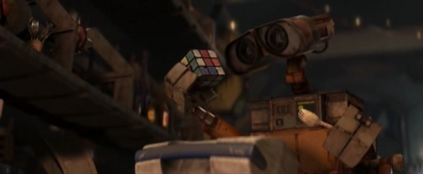 Robot WALL·E has eyes like a binocular. He looks interested with them at a Rubik's cube.